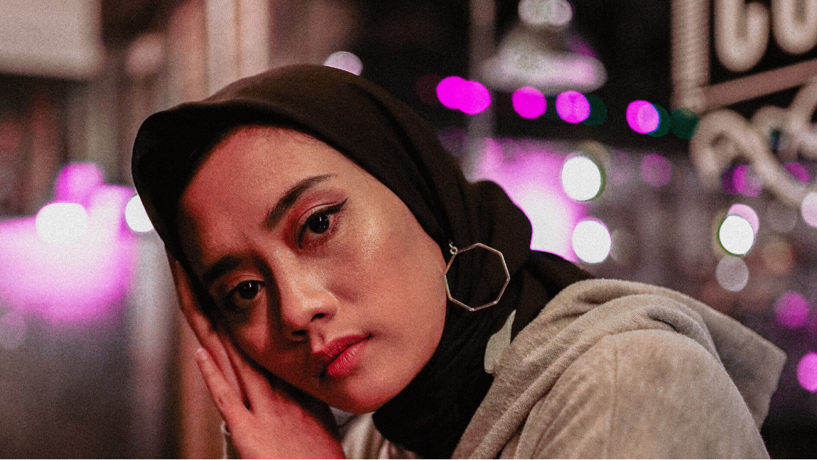 [Image description: A woman in a black hijab tilts her head on her hands and look straight into the camera. The background is a collection of magenta bokeh lights.] via Unsplash