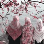 [Image description: Three women stand shoulder to shoulder under a tree with pink leaves. All the women are wearing hijabs. Each woman's hijab has a different pattern on it with varying shades of pink. They all stare out into what seems to be groups of mountains.] via Unspalsh
