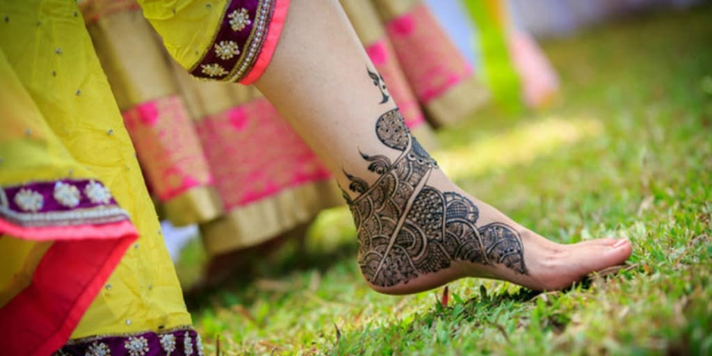 [Image description: Foot decorated with henna is lifted slightly.] via Pexels
