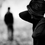 [Image description: Woman holds her hair back, looking down. A man's figure stands in the distance.] via Pexels