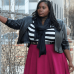 A black woman stands wearing a pink skirt, striped shirt, jacket and black scarf. Via Stylish Curves