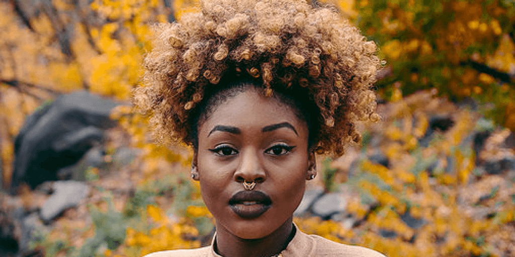 A woman with a nose ring in front of an orange backdrop stares at the camera. Via Tumblr