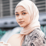 [Image description: Woman with a headscarf looks intently at the camera.] via Pexels