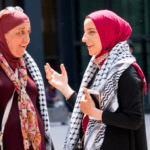 [Image description: Two women wearing headscarfs and checkered keffiyehs have a conversation.] via Flickr