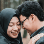 [Image description: A woman wearing hijab laughs while leaning against a man.] Photo by vjapratama from Pexels