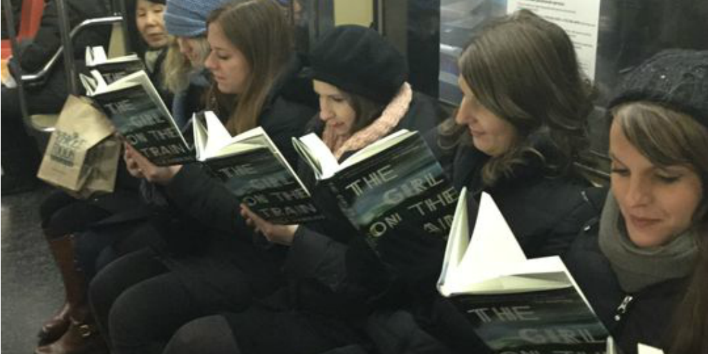 Multiple women sitting on a train and reading novels.
