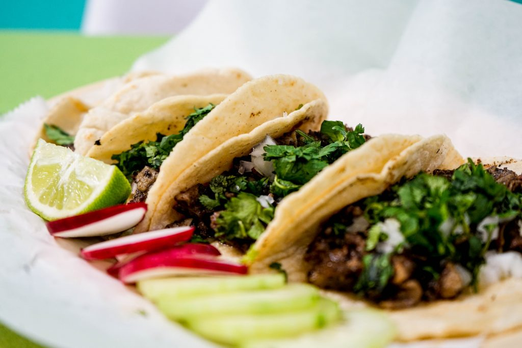 Tacos filled with meat, topped with herbs on a plate.