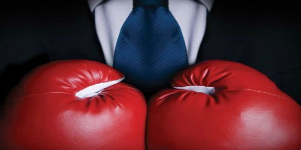 A close up of a man in a suit and tie as he holds boxing gloves to his chest