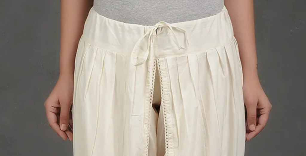 A pair of cream colored dhoti pants tied with a string.