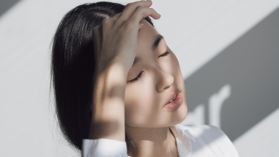 [Image description: Woman holds her forehead, eyes closed in the light.] via Unsplash