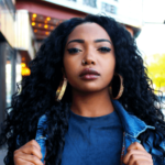 A woman wearing a blue jacket and blue shirt stares at the camera Clarke Sanders on Unsplash
