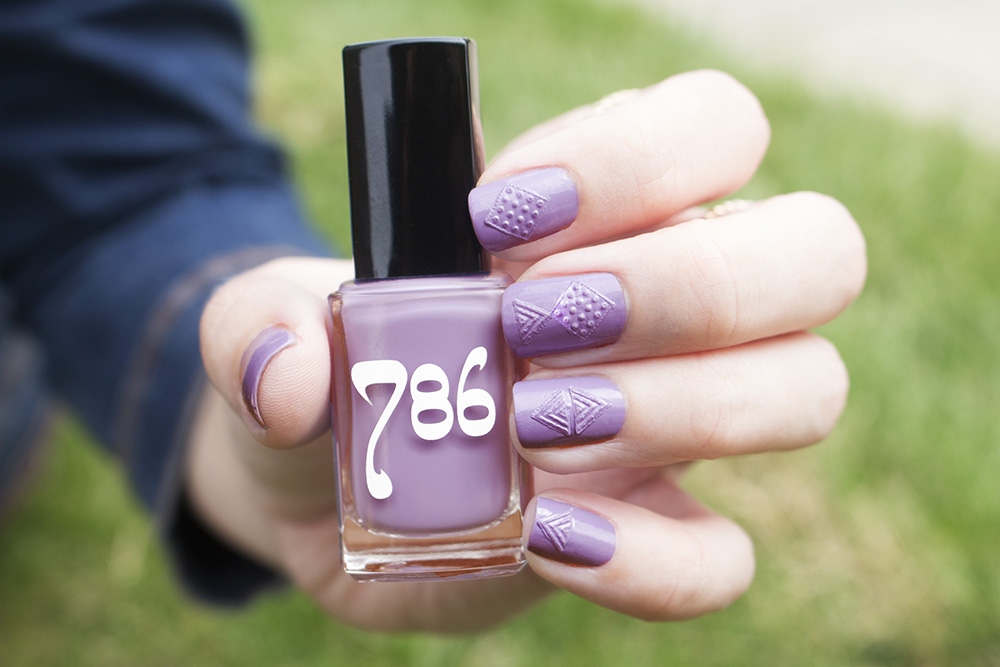 "[Image Description: A left hand, nails with a printed pattern and painted lavender , holding onto a bottle of nail polish labeled ""786"" against the grass.]"