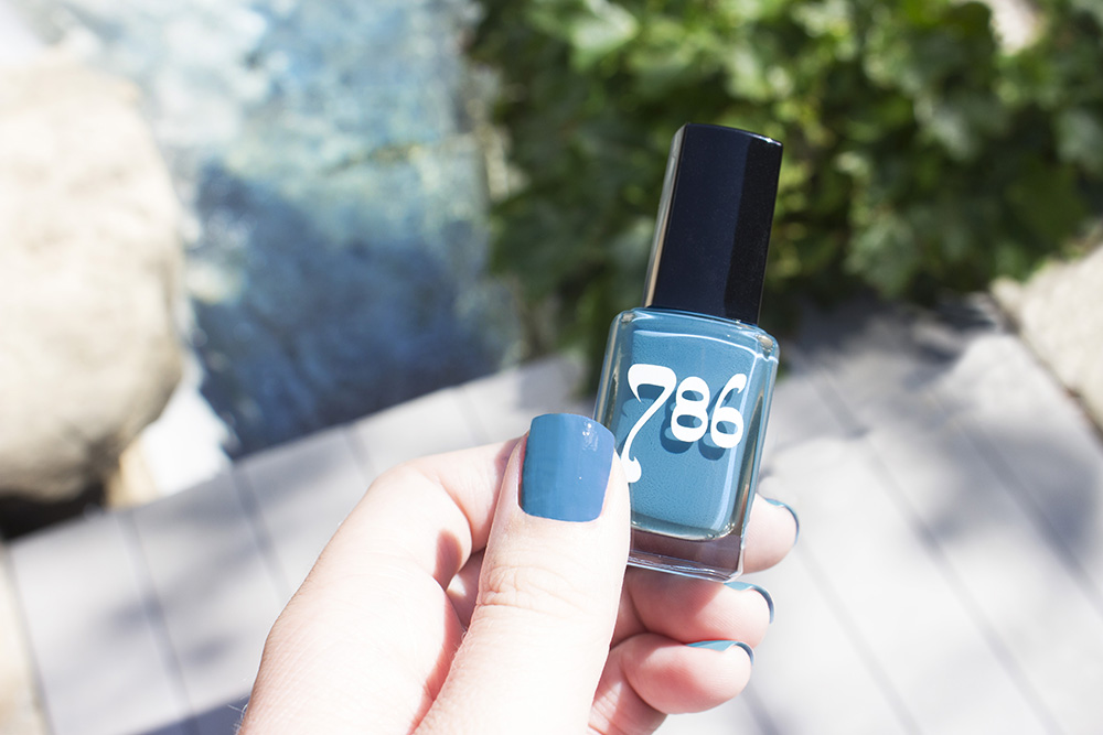 "[Image Description: A left hand, with its nails painted dark blue, holding a blue bottle of nail polish labeled ""786""]"
