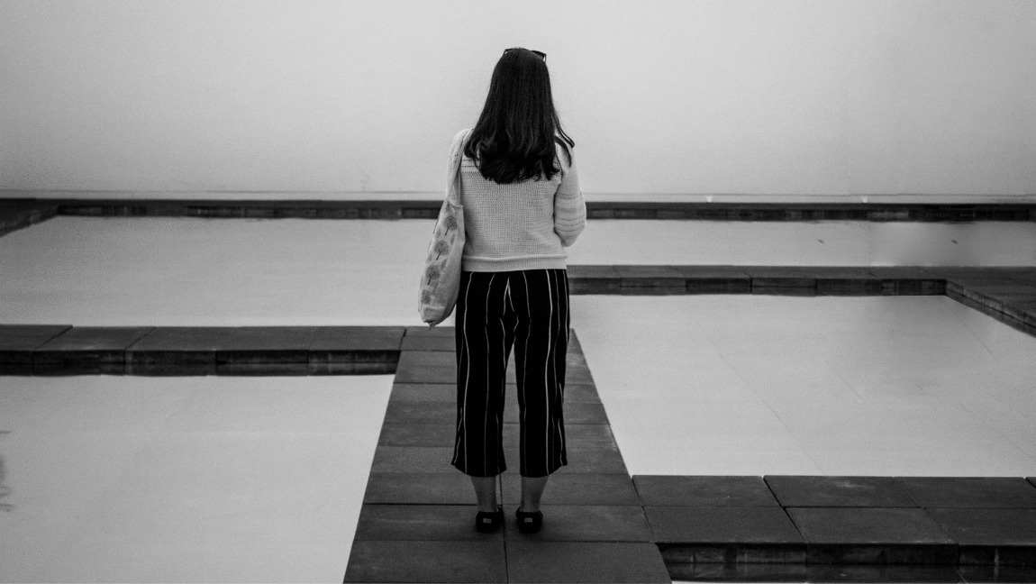 A black and white photo of a woman standing alone in an empty room. The woman is dressed in striped pants and a sweater.
