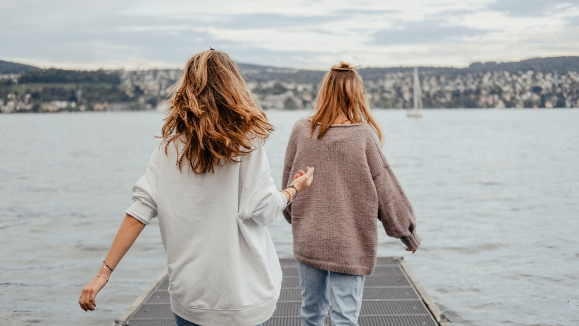 Two girls walk down a bridge that leads to a vast body of water. Both of the girls are wearing cardigan sweaters, while their hair is blowing in the wind. Infront of them, across the large body of water, is land with buildings on it.