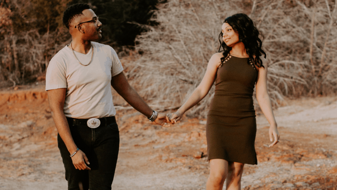 [Image description: Man holds hands and walks with a woman.] Photo by Jasmine Wallace Carter from Pexels