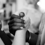 A white person and a black person holding hands.