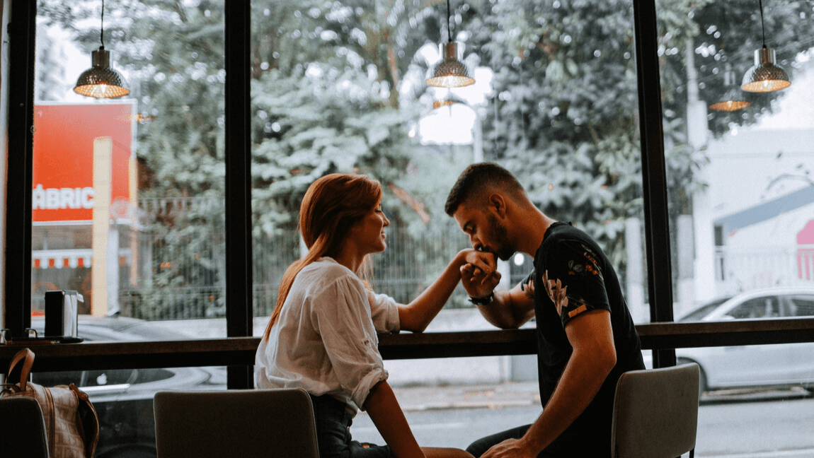 [Image description: selective focus photography of man and woman sitting on dining set with man kissing hand of woman.] via Unsplash