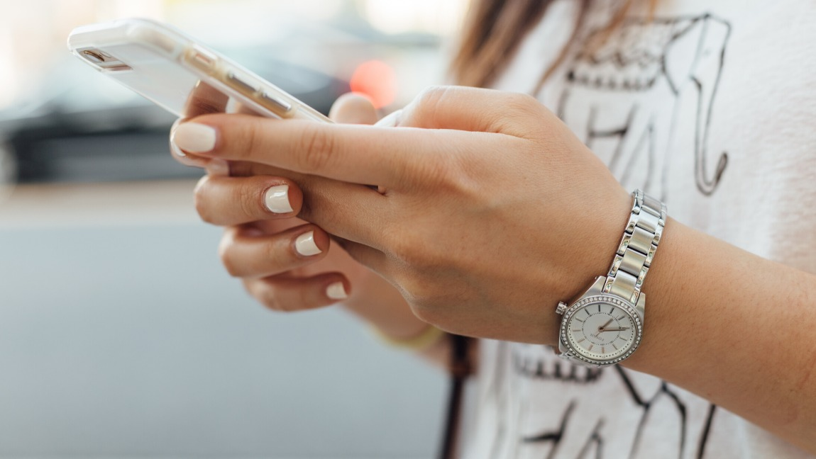 A woman holds her phone in her hands while she is texting. Her nails are manicured and she wears a watch on her left hand.
