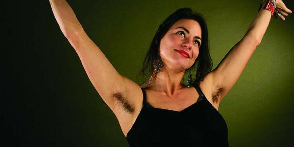 A woman before a green background with armpit hair. Via tntdownunder.com