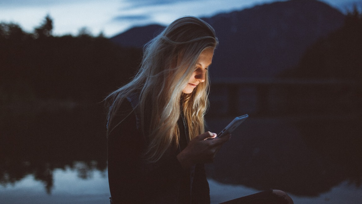 A girl with long blond hair has her phone in her hand, and she is staring at it pointedly. The background is dark and gloomy, but the light of the phone screen illuminates her face.