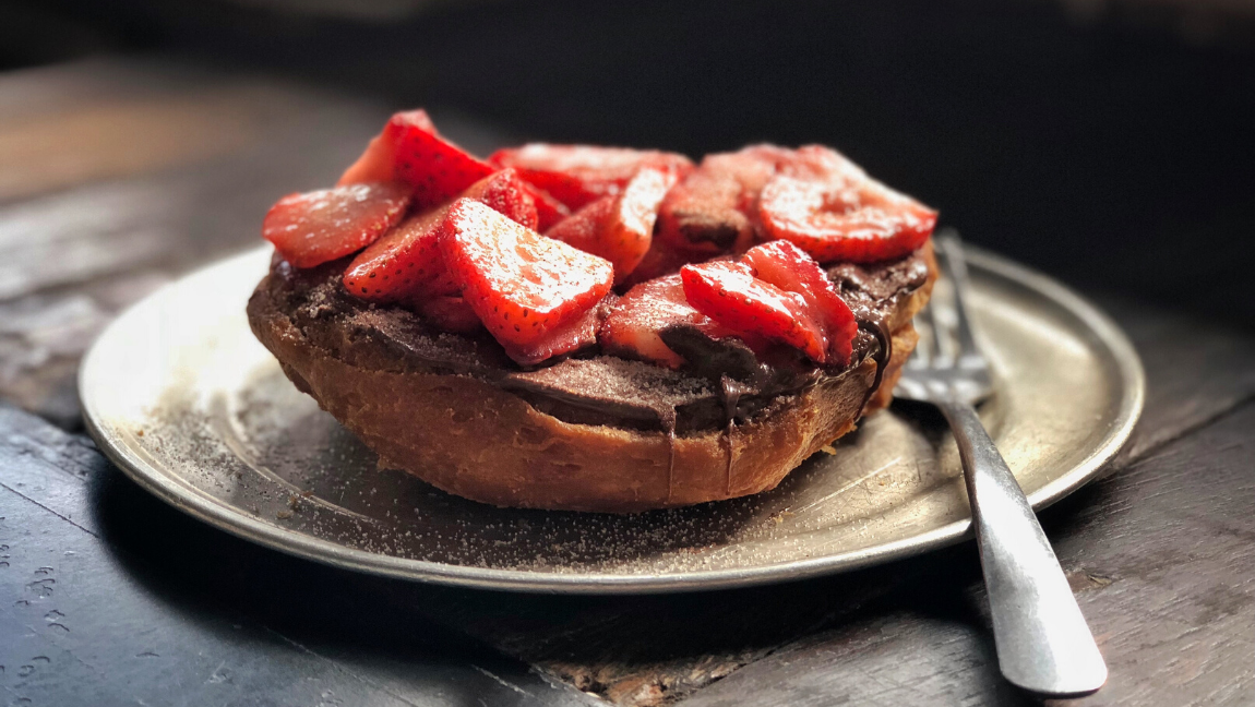 [Image description: Slice of toasted bread with nutella and strawberries on a plate, a fork next to the food.] via Unsplash