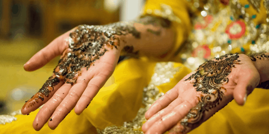 [Image description: Woman's hands shown with henna designs.] via Unsplash