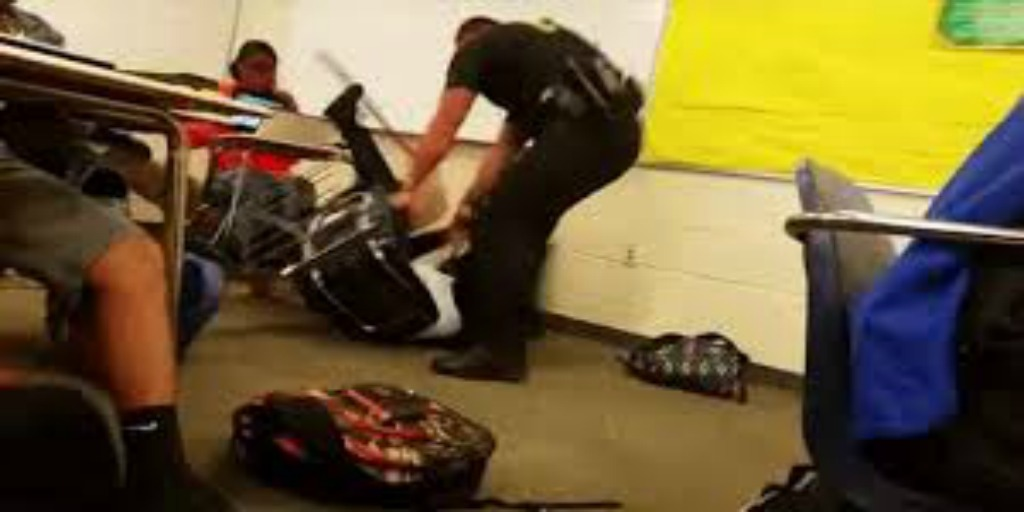 Still from a video of a police officer beating up a black girl.