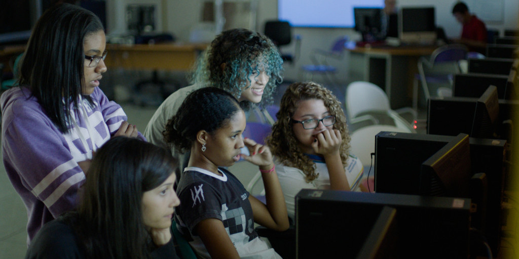 Diverse women crowded around a computer.