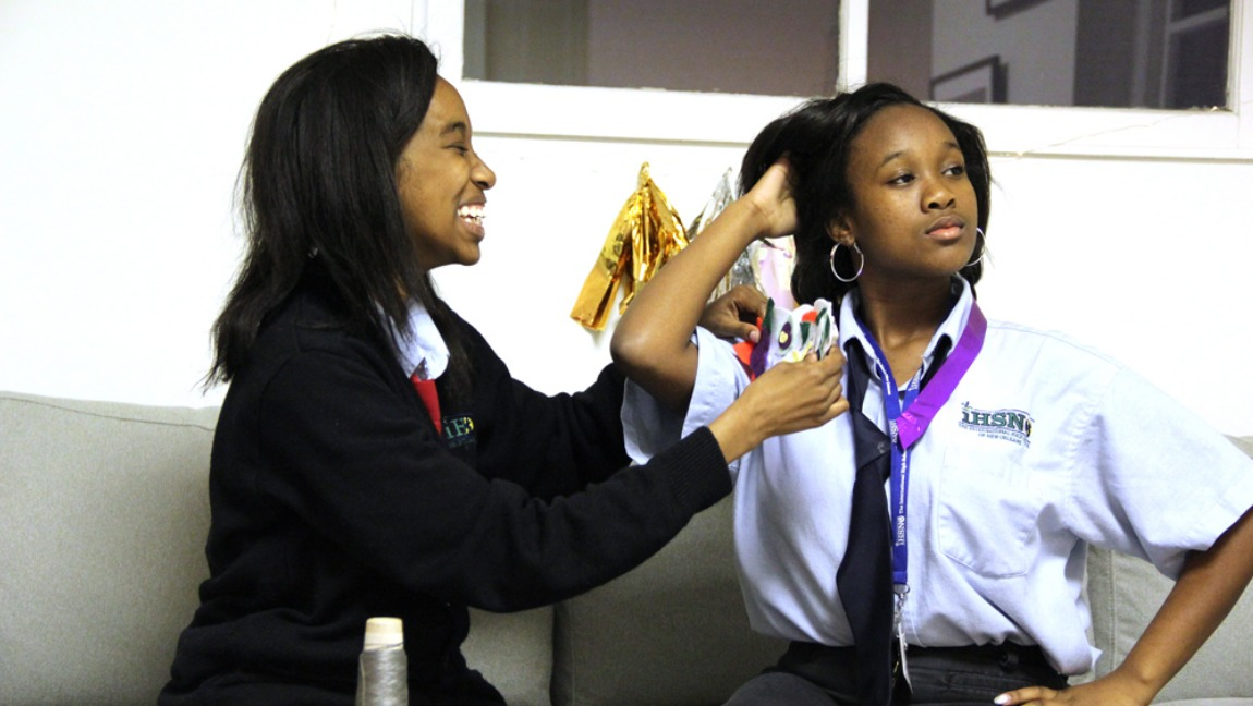 Two girls in school uniforms sit on a couch, the girl on the right poses as the other girl laughs, placing fabric on her shoulder.
