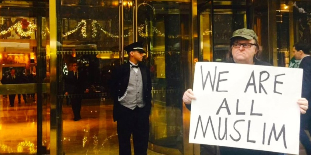 "michael moore holds a sign saying ""We are all Muslim"