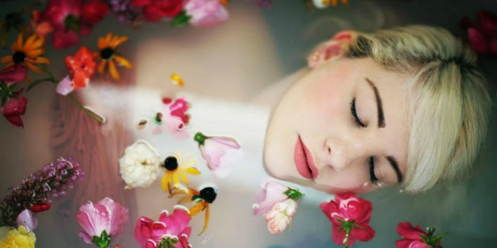 [Image attribution: Woman lays in a bathtub, flowers floating around her.] Photo via Unsplash