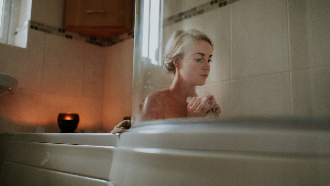 [Image description: Woman sits in a bathtub.] via Unsplash