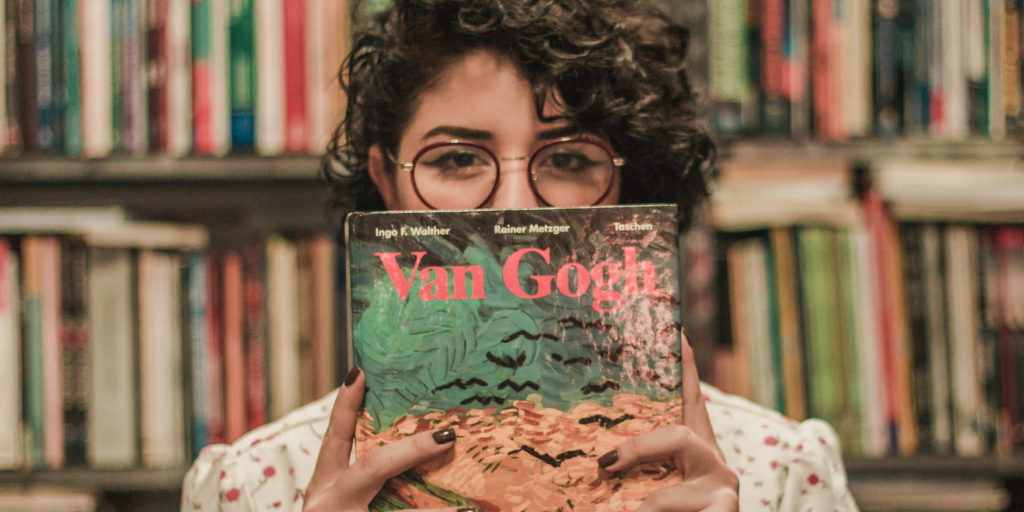 [Image description: Woman stands in front of bookshelves, holding a Van Gogh book up to her face.] via Unsplash