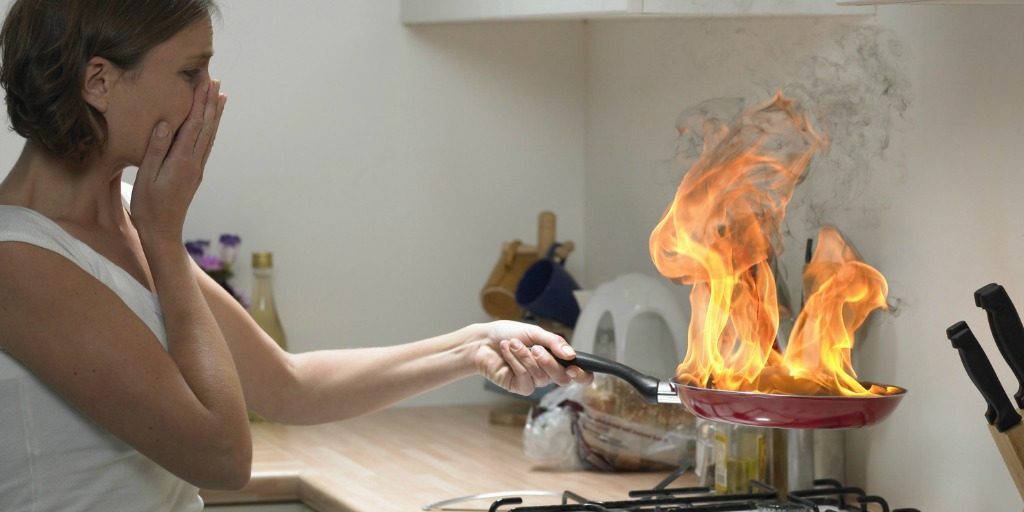 woman-with-hand-to-face-holding-burning-frying-pan