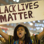 A protester holds a banner against black segregation in a improvised demonstration throughout Central London in sympathy with the Ferguson protests in the US and the death of Michael Brown who was shot dead by a police officer. Green Park, London. 26 November 2014. Daniel Leal-Olivas/PA