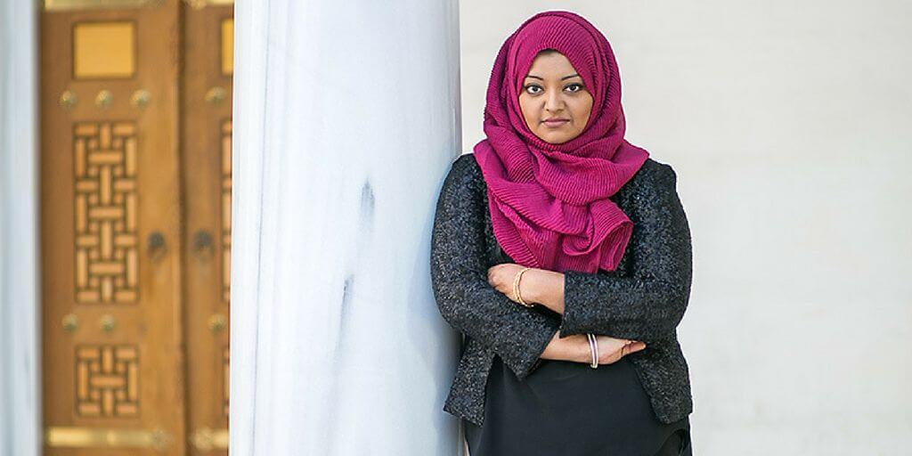 An image of a woman wearing a black suit and pink hijab. Via ayeshaahmadphotography.com