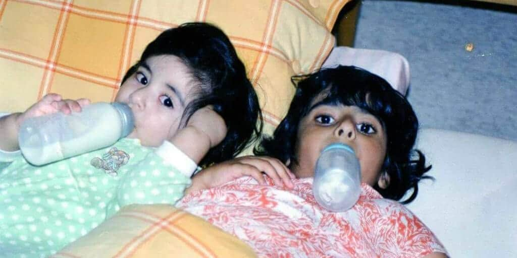 Two young children laying in bed, drinking from bottles.