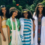 [Image description: Young Ethiopian women stand, holding each other and smiling.] via Pexels