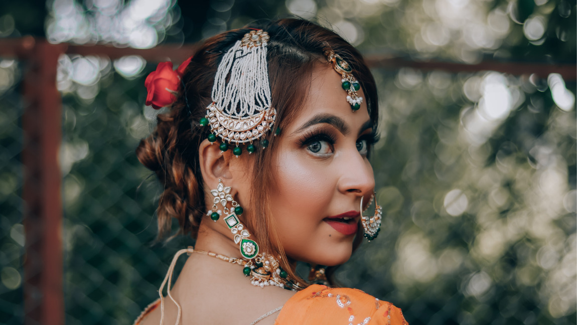 A woman dressed in a traditional wedding attire wearing make up and traditional Desi jewelry.