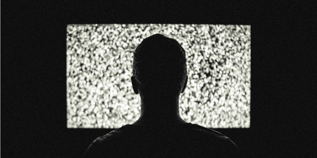 Silhouette of a person watching a staticky movie screen.