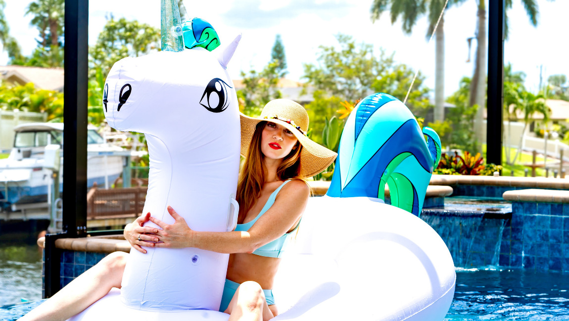 Woman in a swim suit and sun hat on a unicorn float in a pool