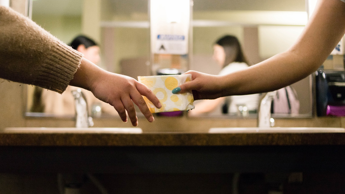 The arm of one woman passing a yellow pad to the arm of another woman in a bathroom