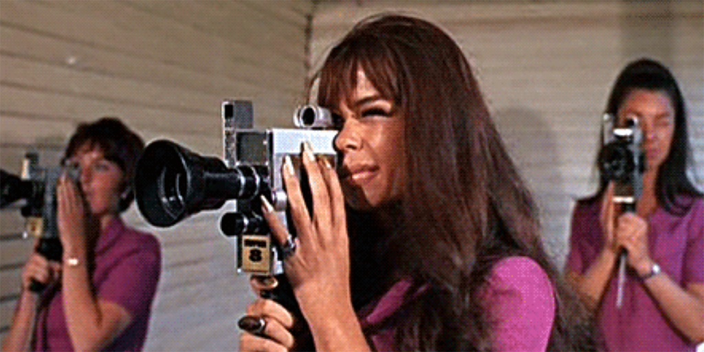 A woman with brown hair filming a scene.
