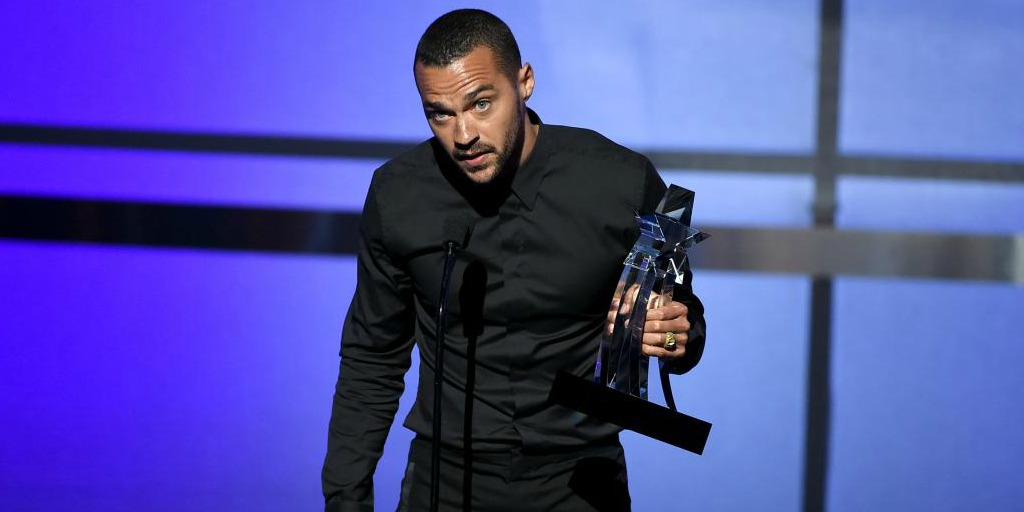 Jesse Williams holding his Humanitarian Award.