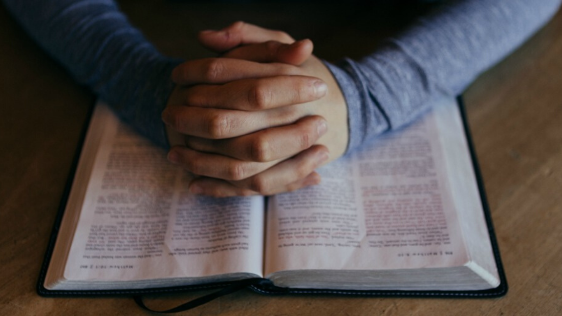 [Image description: Hands clasped over book.] via Pexels