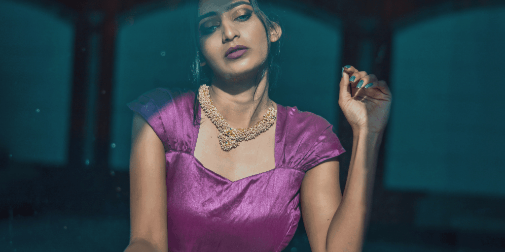 [Image description: Woman in a purple dress stares outside.] Photo by HARSH KUSHWAHA from Pexels