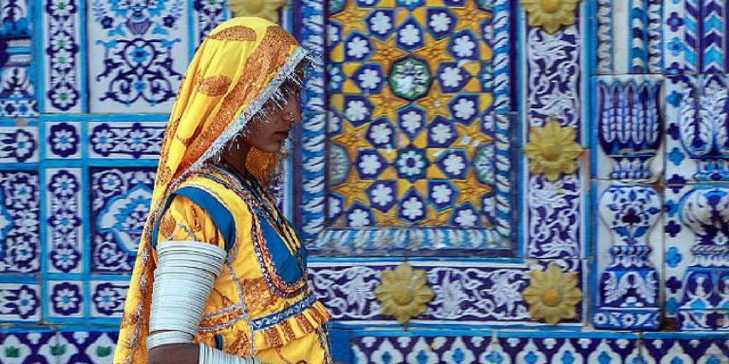 [Image description: Woman in traditional wear walks by a mosaic wall] Photo by Nadeem Khawar