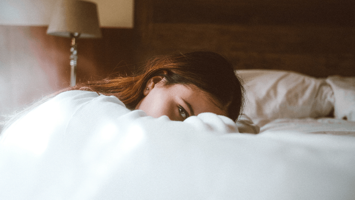 [Image description: Woman laying on bed looks directly into the camera.] Photo by Bruno van der Kraan on Unsplash