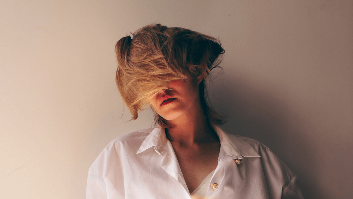 A blonde woman sits dejectedly against a white wall. Her hair covers her face.